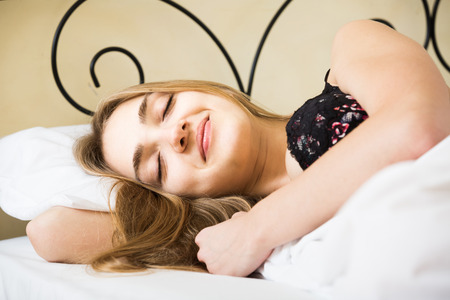 wellness sleepy: adult spanish woman lying in bed under sheet with closed eyes