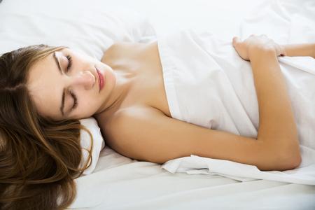 wellness sleepy: Brunette girl sleeping on white pillow in bed in home interior