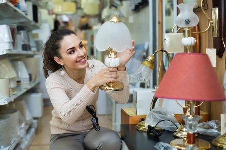 interior lighting: Adult woman selecting lighting units for interior in household store