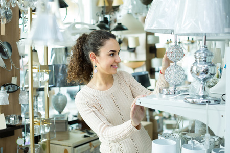 bright housekeeping: Young female customer buying interior lights for home in mall
