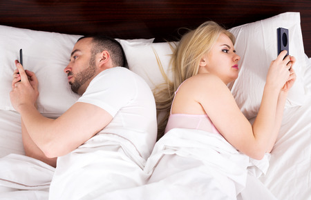socialising: Man and woman socialising with mobile phones in bed Stock Photo