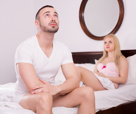 impotent: Unsatisfied wife and her sad young husband having difficulties in bed Stock Photo