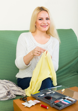 mending: Attentive  longhair girl on couch mending linen and smiling Stock Photo