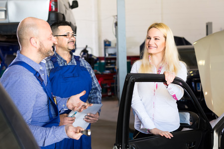 two car garage: Happy woman has brought her car to dealership for maintenance service Stock Photo