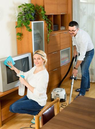 marido y mujer: Alegre marido ayudando a su joven esposa sonriente rubia de la limpieza de la habitaci�n. Centrarse en la mujer Foto de archivo