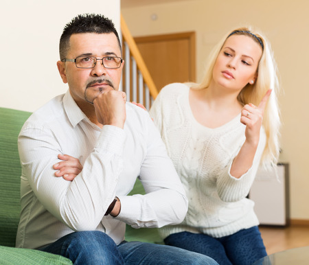 jackboot: Family quarrel. Sad man and his angry young blonde wife during quarrel in living room at home