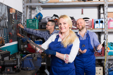 35 40: Auto service center positive crew portrait near tools and equipment. Focus on girl