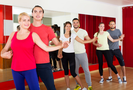 unprofessional: Group of positive smiling  adults dancing salsa in club Stock Photo