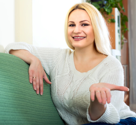 blonde streaks: Beautiful blond woman sitting on a sofa indoors stretching her arm with palm up to the viewer