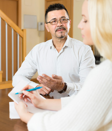 census: Man answer questions of young female social worker with papers at the table Stock Photo