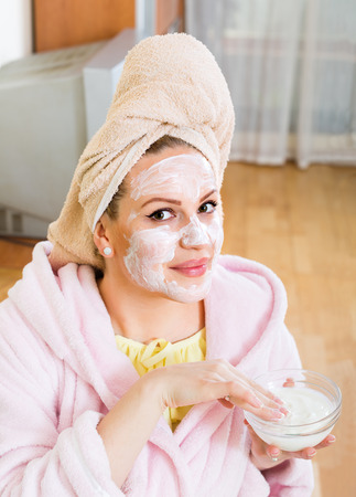 house robes: Positive  girl  in bathrobe putting cosmetic treatment on face