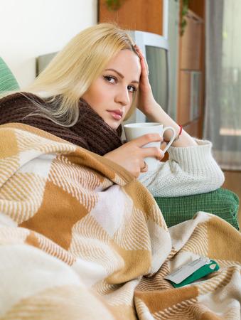 persona enferma: Mujer joven con la bufanda, manta y la medicina disolver en vidrio Foto de archivo
