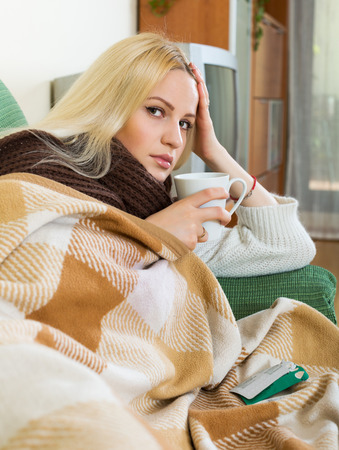 sick person: Young woman with scarf, blanket and dissolving medicine in glass Stock Photo