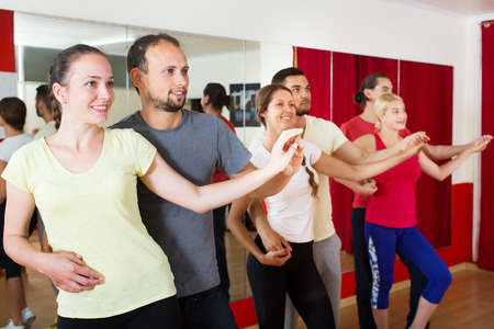 unprofessional: Smiling happy adults dancing bachata together in a dance studio