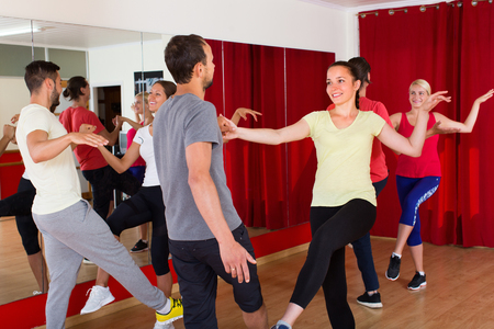 unprofessional: Group of cheerful adults dancing active dance in class. Selective focus Stock Photo