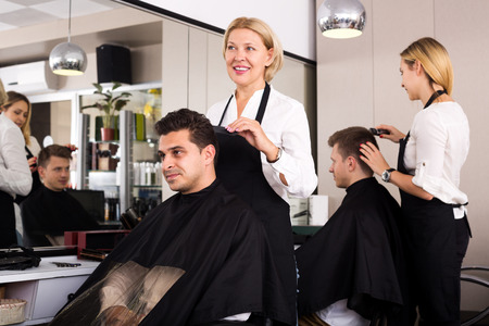 haircutter: Smiling female doing hairstyle for adult man in hairdressing saloon Stock Photo