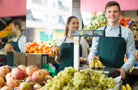 30 to 35: Smiling supermarket workers selling stems of sweet bananas. Focus on man Stock Photo