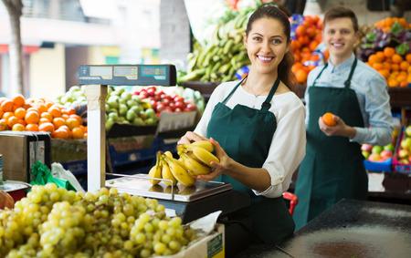 Personal amable en delantales de venta de plátanos dulces en el mercado