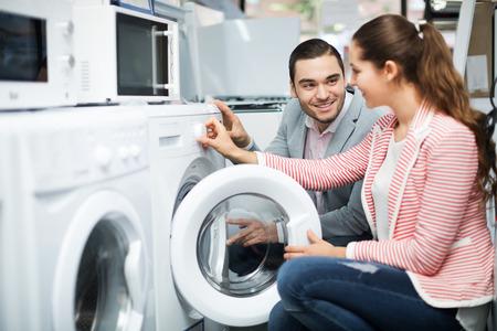 cargador frontal: Joven pareja elegir lavadora en el hipermercado y sonriente