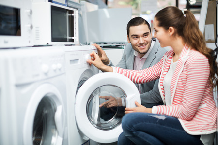 front loader: Young couple choosing washing machine in the hypermarket and smiling