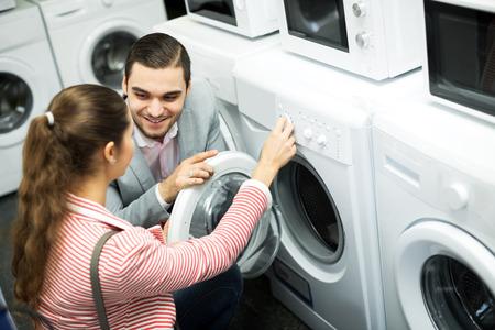 lavadora con ropa: Pareja joven familia feliz comprar nueva lavadora de ropa en un supermercado. Centrarse en la mujer
