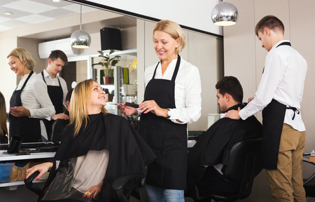 16s: Positive aged woman cutting girl hair in the barbershop Stock Photo