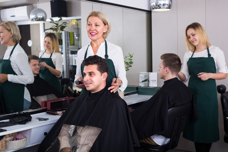 19's: Smiling elderly female hairdresser cutting hair of brunet guy in barbershop. Focus on man Stock Photo