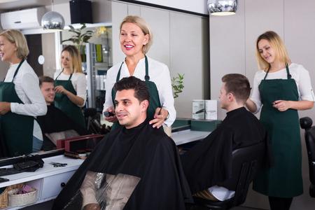 19's: Smiling elderly female hairdresser cutting hair of brunet guy in barbershop. Focus on man Stock Photo