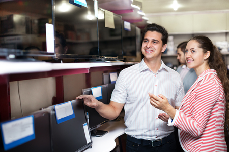 flat screen: Young people purchasing flat screen television set at a electronics store