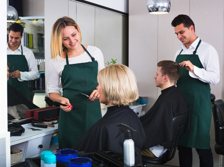 cutting hair: Young smiling woman cutting female pensioner hair in hairdressing saloon