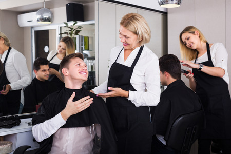 16s: Happy senior female hairdresser serving teenager guy in chair