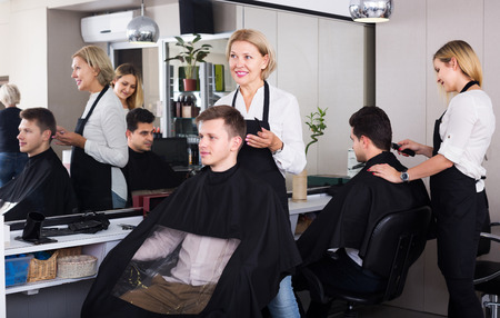 19's: Positive senior woman hairdresser serving teenager guy in chair