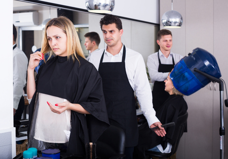 Blond young woman complaining on new haircut in hair salon