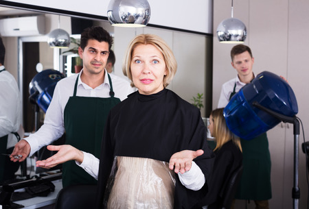 bad hair: Furious mature woman screaming on hairstylist as hair cut badly Stock Photo