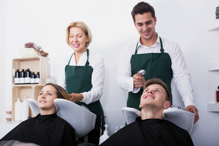 19's: Portrait of pleased customers and smiling hairstylers washing hair in salon. Focus on the right guy Stock Photo