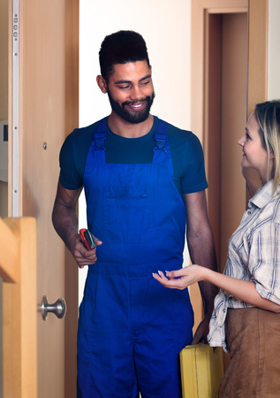 blue overall: Blonde girl meeting African handyman in blue overall at the doorway