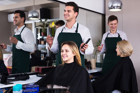 18's: Professional hairdresser cuts hair of blonde girl at the hair salon
