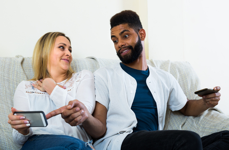 25s: Black man and white woman 25s sitting on sofa with mobiles