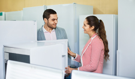 domestic appliances: Young  beautiful couple looking at large fridges in domestic appliances section