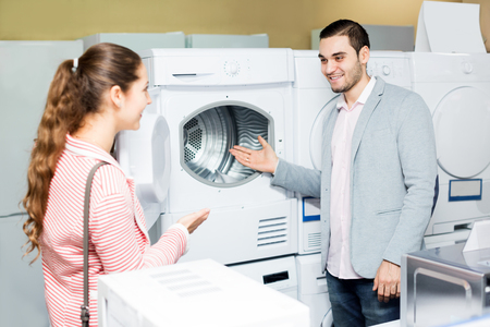 clothes washer: Cheerful family couple buying new clothes washer in supermarket. Focus on the man Stock Photo