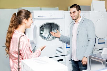 lavadora con ropa: pares de la familia Alegre comprar nueva lavadora de ropa en un supermercado. Centrarse en el hombre