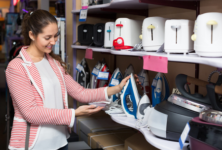 domestic appliances: Young female customer looking at irons in domestic appliances section Stock Photo