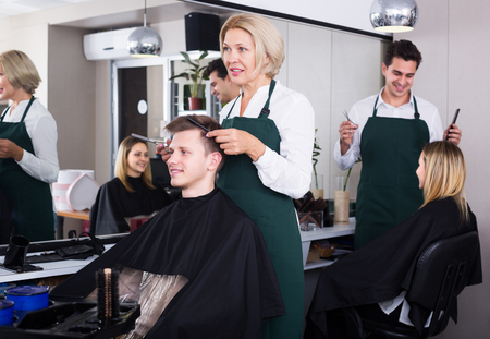16s: Smiling senior woman hairdresser serving teenager guy in chair