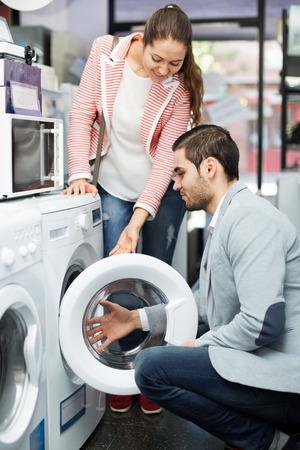 cargador frontal: Joven pareja elegir lavadora en un hipermercado y sonriente Foto de archivo