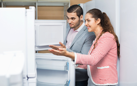 domestic appliances: Satisfied smiling couple looking at large fridges in domestic appliances section Stock Photo
