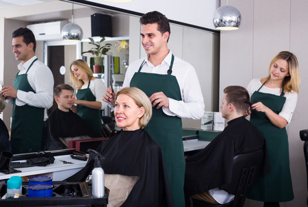 barber chair: Cheerful indian man doing hairstyle for mature woman in hairdressing saloon