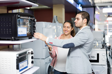 couple famille positive de choisir une nouvelle micro-ondes dans un supermarché. Focus sur l'homme