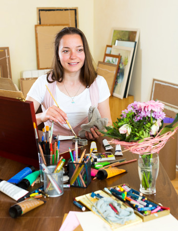 contentedness: Happy adult artist paints a picture at home