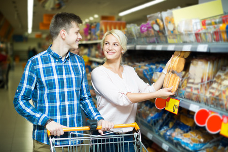 30 35: Attractive young customers choosing bread and pastry in food shop. Focus on the woman