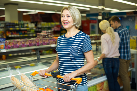 frozen meat: Practical women choosing frozen meat and provision in food store